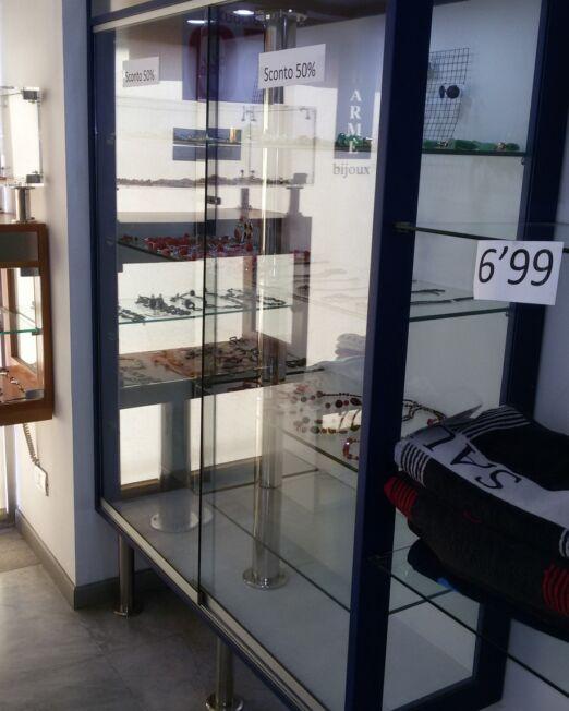 Espositore vetrina in legno blu con ante in vetro scorrevoli con base con piedi in acciaio inox. Misura 160 x 170 h x 50 cm.